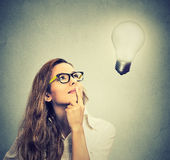 Girl thinks looking up at bright light bulb. Closeup beautiful girl thinks looking up at bright light bulb  on gray wall background. Idea, business, education Stock Photos