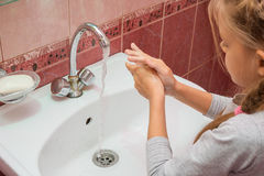 Girl thoroughly wash their hands with soap. And water Stock Photography
