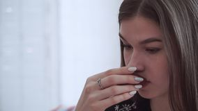 A girl with a thoughtful look drinks a delicious tea from a small Cup.  stock footage