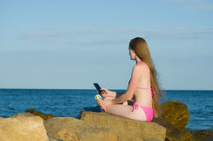 Girl thoughtfully looking into the phone, in a bathing suit on the beach Stock Photos