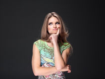 Girl in thoughtfulness. Beautiful girl is thinking with finger to here mouth Stock Photo