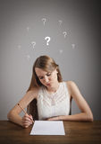 Girl in thoughts. Question marks. Royalty Free Stock Photography