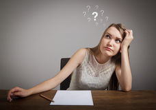 Girl in thoughts. Question marks. Stock Photo