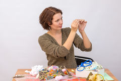 Girl thread a needle at the table with needlework Stock Image