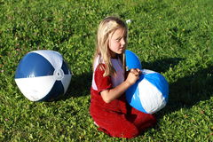 Girl with three balls. Little girl in red dress kneeing with blue and white balls royalty free stock photos