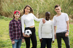 Girl and three boys playing football in spring park and smiling. Happy girl and three boys playing football in spring park and smiling Stock Images
