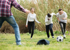 Girl and three boys playing football in spring park and smiling royalty free stock photo