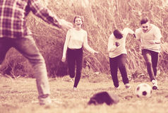 Girl and three boys playing football in spring park and smiling Stock Photo