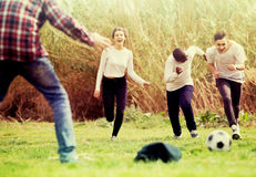 Girl and three boys playing football in spring park and smiling Stock Photography