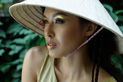 Girl in a three-cornered hat looking away. Against a background of green foliage Royalty Free Stock Photography