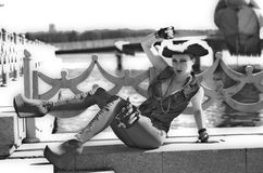 Girl in a three-cornered hat on the river bank. Girl in pirate hat posing on the river against the background of the ship WIG Stock Photo