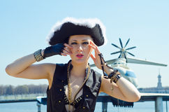 Girl in a three-cornered hat on the river bank. Girl in pirate hat posing on the river against the background of the ship WIG Royalty Free Stock Image