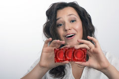 Girl with  with three red condom packs Stock Photo