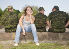 The girl and three soldiers Stock Photography