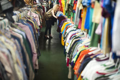 Girl thrift store shopping 3. Girl looking at rows of colorful t-shirts in a thrift shop Stock Photos
