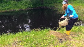 Girl throw fishing bag with net in the pond. stock video footage