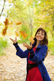 Girl throw up maple leaves Stock Images