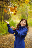 Girl throw up yellow leaves Royalty Free Stock Photography