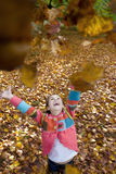 Girl throwing autumn leaves in air Stock Images
