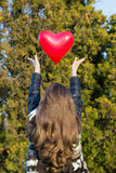 Girl throwing a balloon in the shape of heart Royalty Free Stock Photo
