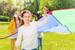 Girl throwing balls up playing parachute game. Portrait of smiling girl throwing small balls up by using colorful parachute with her friends stock photography