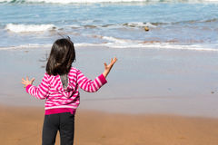 Girl throwing a boulder into the sea Royalty Free Stock Images