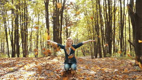 Girl throwing leaves in Autumn in slow motion stock footage