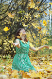 Girl throwing maple leaves in the air Royalty Free Stock Photography