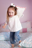 Girl throwing a pillow Stock Photos