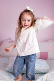 Girl throwing a pillow Stock Photography