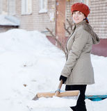 Girl throwing snow  with shovel Royalty Free Stock Photography