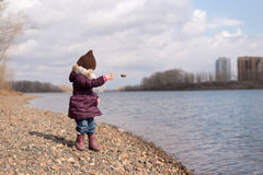 Girl throwing a stone into river Stock Photography