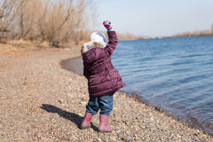 Girl throwing stones into river Stock Image