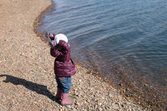 Girl throwing stones into the river Royalty Free Stock Photography