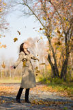 Girl throwing yellow maple leaves in the air Royalty Free Stock Image