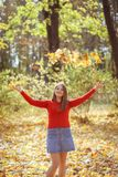 Girl Throws Autumn Leaves In Forest And Smiles Stock Photo