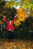 The girl throws autumn leaves upwards Royalty Free Stock Photos