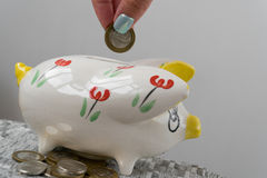 The girl throws a coin into the piggy bank. Piggy bank in the form of a painted pig. A handful of coins Royalty Free Stock Photography
