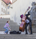 A girl throws a coin street musician in gratitude for his music Stock Images