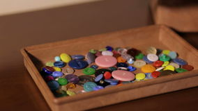 Girl throws colored buttons in the box. stock video footage