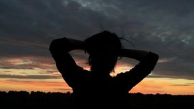 Girl throws hair and straightens hair. The action takes place at sunset. Girl plays with hair stock video