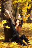 The girl throws leaves. The girl on autumn leaves Stock Photos