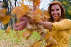 Girl Throws Leaves. A 24 year old redhead caucasian female plays with fallen leaves on a windy autumn day in New England, USA stock photography