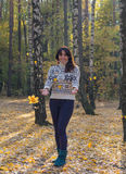 Girl throws leaves in autumn forest Stock Image