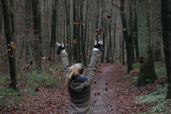 Girl throws leaves in the forest Royalty Free Stock Images