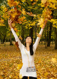 A girl throws leaves Stock Photography