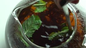 Girl throws mint leaves in a tea stock video