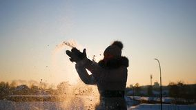 A girl throws snow above her head on sunset background. A girl throws snow above head stock video footage