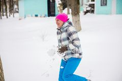 The girl throws snow in the Park, against the trees. The girl throws the snow in the Park , playing snowballs on a background of trees, winter holiday Stock Images