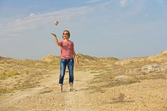 Photo taken in summer. The girl throws a stone and depicts weigh. The girl throws a stone and depicts weightlessness Royalty Free Stock Images